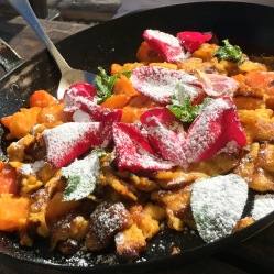 Kaiserschmarren: chopped sweet pancakes with raisins, berries and rose petals
